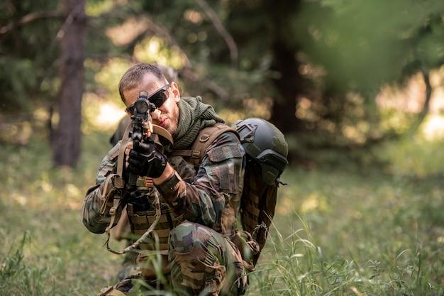 선글라스를 끼고 잔디에 앉아 들판에서 소총을 조준하는 젊은 군인