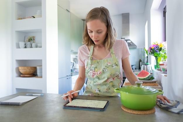 カウンターで大きな鍋の近くのタブレットを使用して、彼女のキッチンで調理している間にレシピをコンサルティングする若い女性に焦点を当てた。正面図。自宅で料理とインターネットのコンセプト