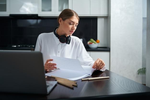 Сосредоточенная молодая женщина в белой рубашке работает с документами, сидя за столом с открытым ноутбуком