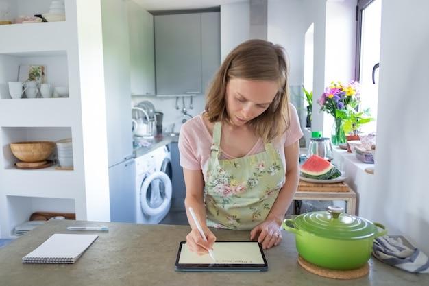 カウンターで大きな鍋の近くのタブレットを使用して、彼女のキッチンで調理している間、パッドの画面に書いて、毎週のメニューを計画している若い女性に焦点を当てました。正面図。家庭料理と家庭のコンセプト