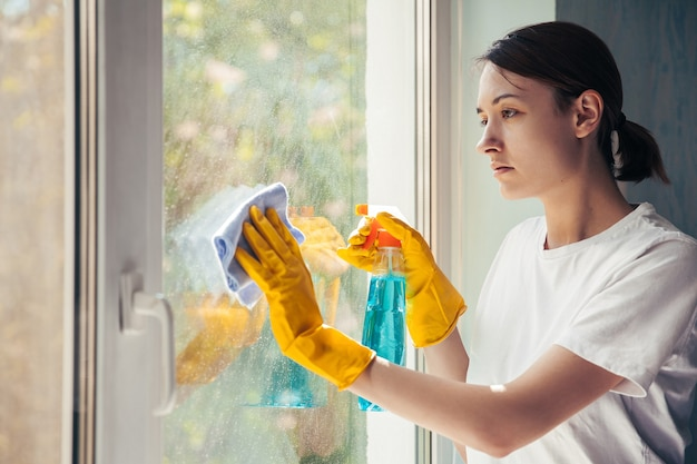 Focused young woman washing window in yellow gloves at home