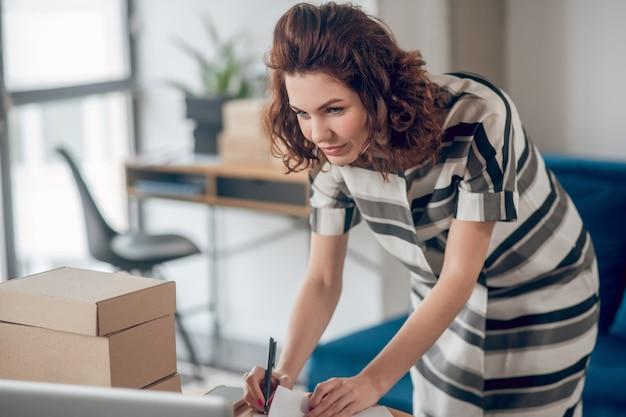 사무실 책상 위에 기대어 손에 볼펜을 들고 집중된 젊은 여성