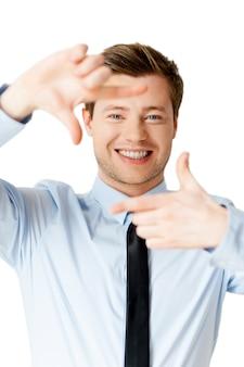 Сосредоточение на тебе. красивый молодой человек в рубашке и галстуке, фокусируясь на вас с рамкой пальца и улыбаясь, стоя изолированно на белом