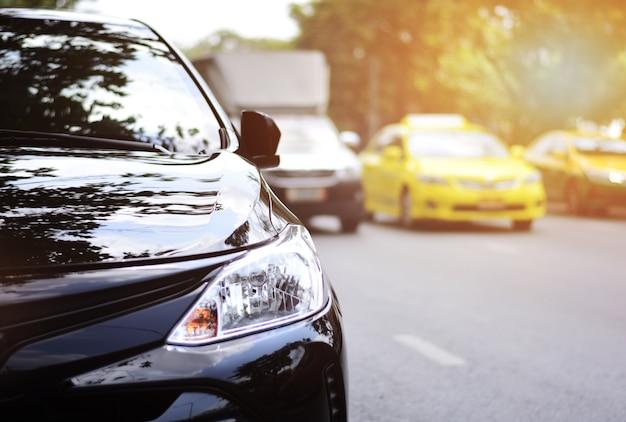 Focusing on the black car headlights on a street corner with sunlight, closeup headlights