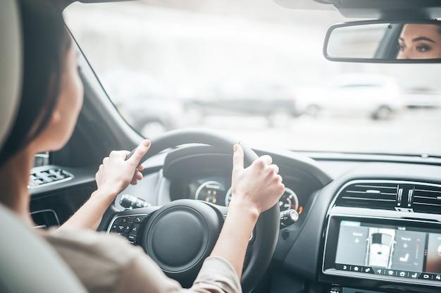 운전에 집중합니다. 차를 운전하는 동안 도로를 바라보는 캐주얼 차림의 매력적인 젊은 여성의 뒷모습