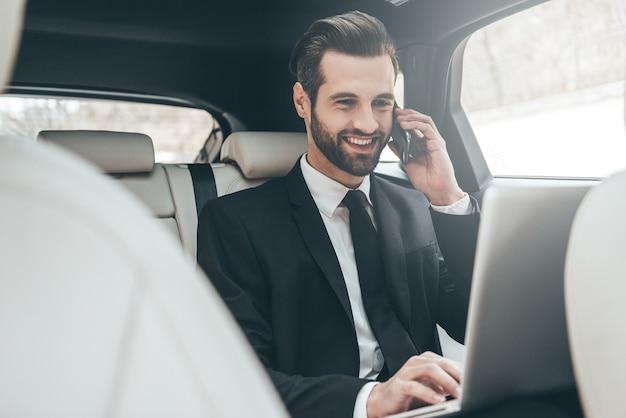 Сосредоточение на работе. красивый молодой бизнесмен работает на своем ноутбуке и разговаривает по телефону, сидя на заднем сиденье автомобиля