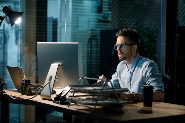 Фокусировка молодого работника поздно в офисе