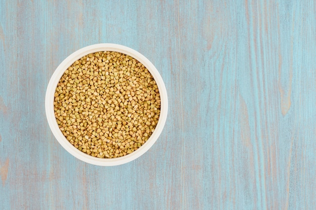 青い木製テーブル、グルテンフリー全粒穀物、fodmapダイエットの白いボウルに緑のそば