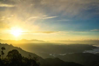 Fog in mountains, fantasy and colorful nature landscape and ray of sunlight through clouds