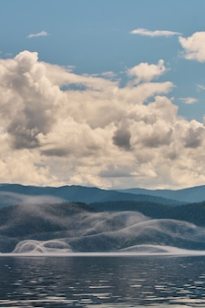 산 계곡에 안개입니다. 알타이 산맥의 호수 위로 아침 안개.