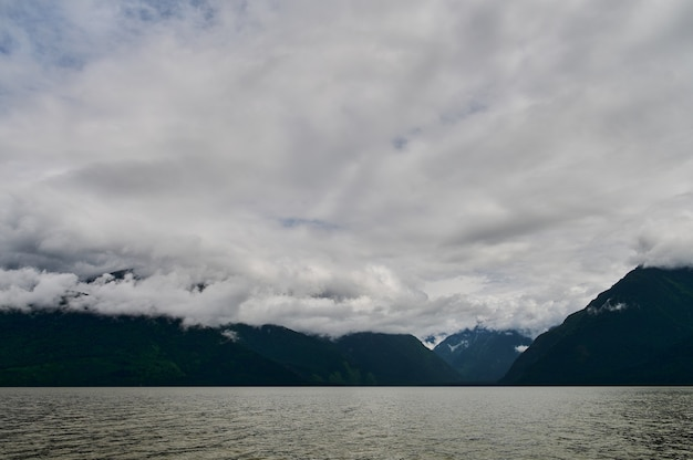 山の谷の霧アルタイ山脈の湖の上の朝の霧