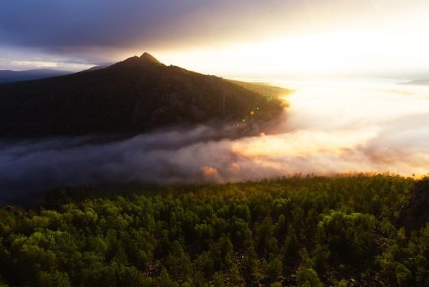 日の出の山の霧。夜明けの山の朝の霧。山の中の雲。雨上がりの朝霧。夜明けの山。ミルクリバー。コピースペース