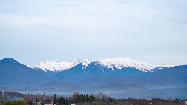 Fog in the mountains, snow-capped peaks, horizontal shot, landscape.