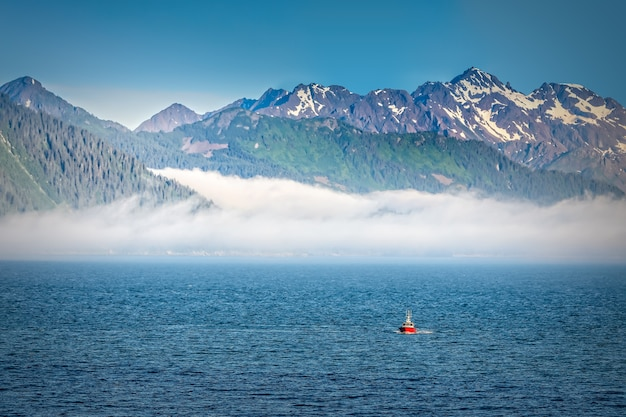 オープンウォーターから見たアラスカの山々に昇る霧