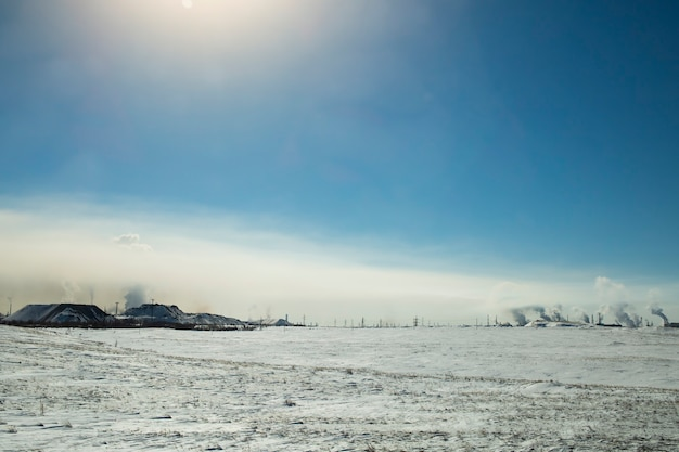 Fog, smoke from chemical production spreads over the ground on a sunny winter day.