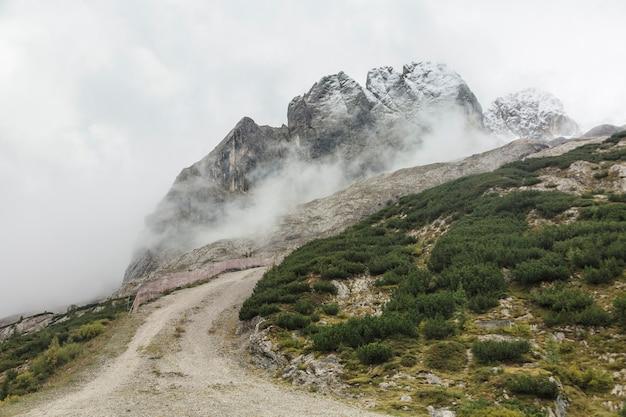 アルプス、ドロミテの岩の霧と曇りの山々の風景
