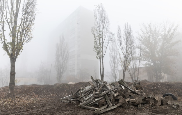 Foggy autumn morning in the city. ecological concept. deep fog on the city street in cold dark autumn morning. dump of concrete structures on the streets