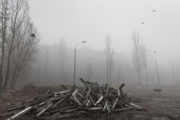 街の霧の秋の朝。生態学的概念。寒くて暗い秋の朝の街の通りの深い霧。路上でのコンクリート構造物のダンプ