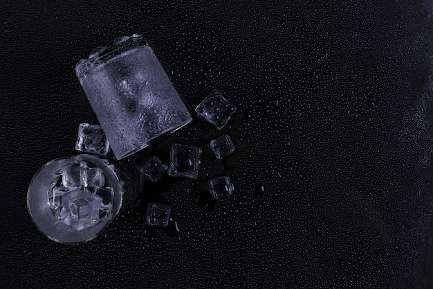 A foggy glass and ice lies on a black background