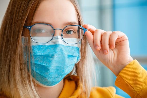 젊은 여자를 입고 안개 안경입니다. 초상화를 닫습니다. 파란색 의료 보호 얼굴 마스크와 안경에 십 대 소녀 복사 공간 흐린 된 안개 낀 안경 정리합니다. 새로운 노멀.