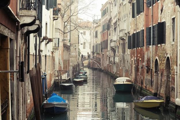 Туманное утро в венеции. вид на узкий канал между старыми зданиями