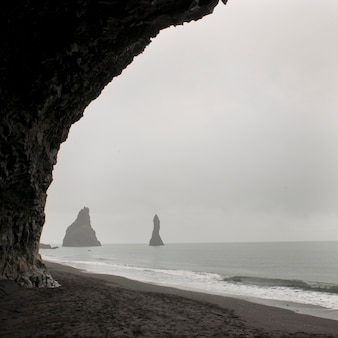 Foggy seascape, framed rock stacks from sea cave