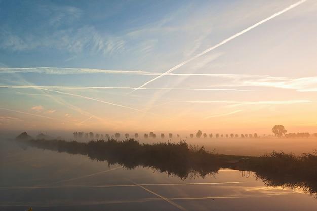 Colpo nebbioso di un bellissimo paesaggio con nuvole danzanti nei paesi bassi