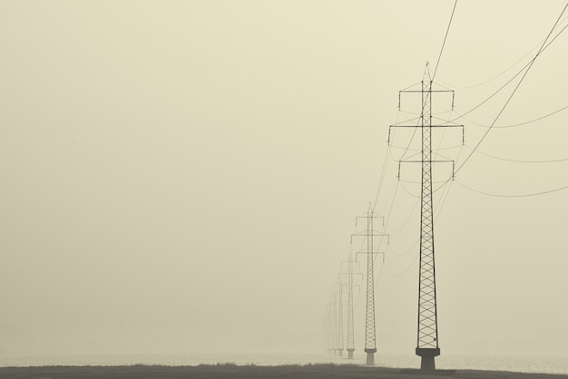 Foggy shot of transmission towers in the middle of a street