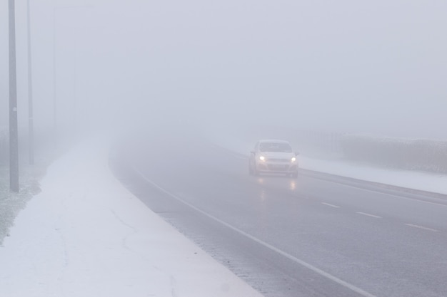 Foggy winter road, cars driving fading into the fog