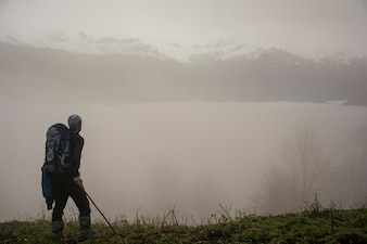 Fogy mountain hills and active hiker with backpack in foreground