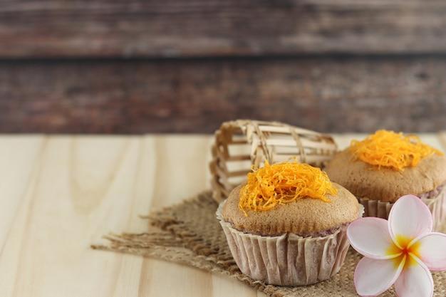 Foi thong banana cake (fios de ovos), thai traditional cusine dessert from yolk on wooden background.