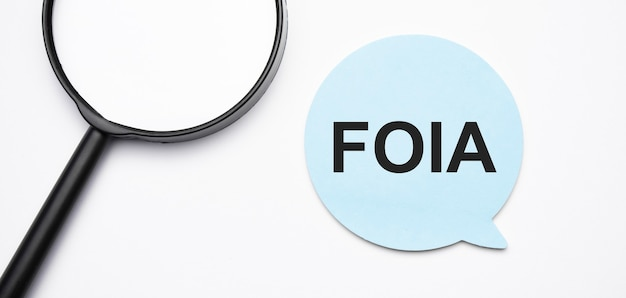 Foia speech bubble and black magnifier isolated on the yellow background.