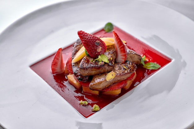 Foie gras in strawberry sauce with pear and strawberry pieces on white plate