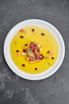 Фуа-гра с соусом, на белой тарелке