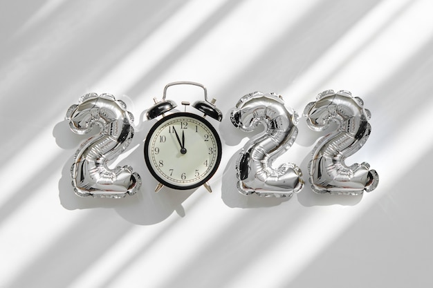 Foil balloons in the form of numbers 2022 and alarm clock. new year celebration. gold and silver air balloons. holiday party decoration.