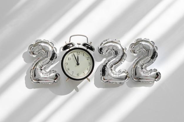 숫자 2022와 알람 시계의 형태로 호일 풍선. 새해 축하. 금색과 은색 공기 풍선입니다. 휴일 파티 장식입니다.