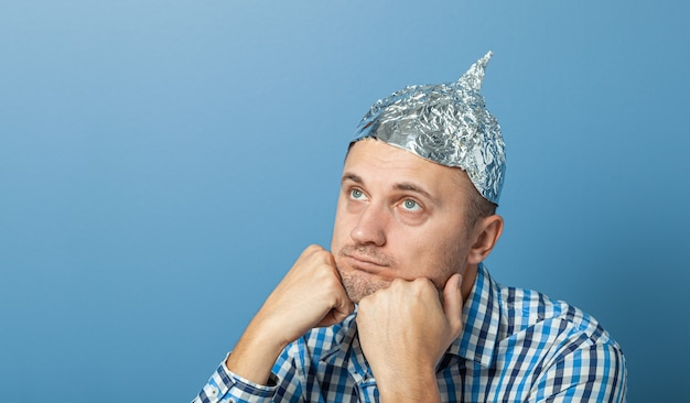 Foil hat on man. man with a bored face. protects from reading think.