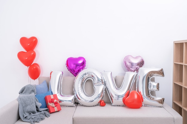 Foil love balloons and gifts on a sofa with white wall in background for valentine's day, mother's day surprise design concept.