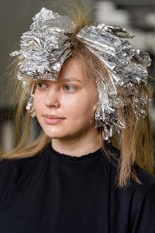 若いモデルの髪にホイル。シャタッシュテクニックを使用したトレンディなヘアライトニング。