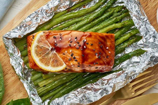 Foil pack dinner with red fish. fillet of salmon with asparagus. oven-baked hot dinner, keto paleo diet