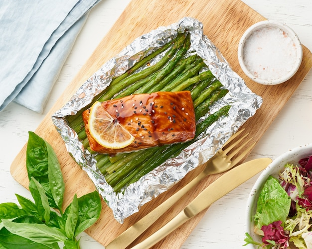 Foil pack dinner with red fish. fillet of salmon with asparagus.