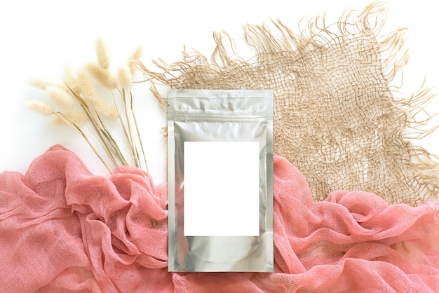 Foil packaging with a pink background, burlap and dried flowers, natural style