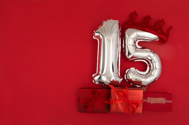 Foil silver air balloons showing number 15 fifteen placed on red background with wrapped presents for concept of birthday anniversary