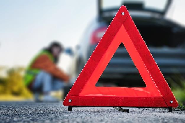 접이식 경고 도로 표지판, 운전자는 백그라운드에서 휠을 변경합니다.