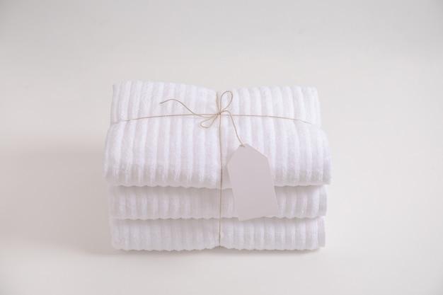 Сложенные и сложенные белые махровые полотенца с пустой этикеткой