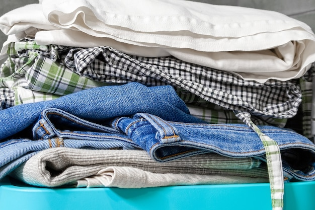 Сложенное постельное белье, джинсы, полотенца на синем ящике. куча белья и одежды для стирки. крупным планом вид