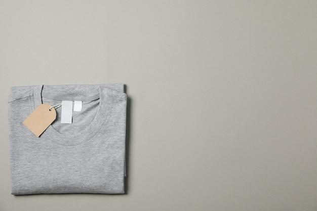 Сложенная пустая серая футболка с биркой на сером