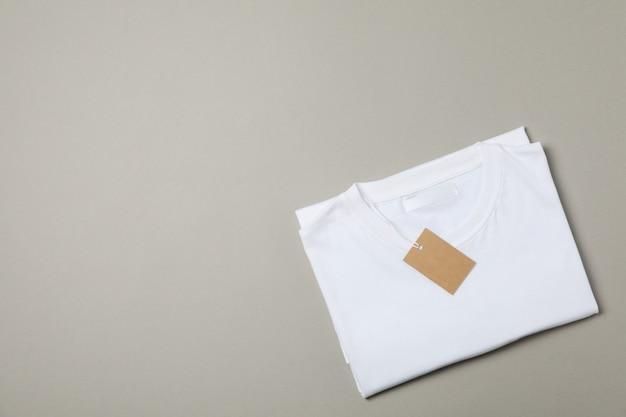 Сложенная пустая белая футболка с биркой на сером