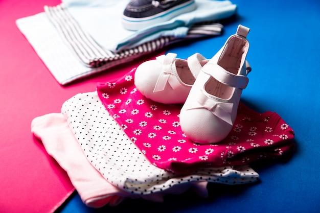 ミニマルなピンクとブルーの上にボートシューズが付いた折り畳まれたブルーとピンクのボディスーツ。新生児の男の子と女の子のおむつ。幼児服のスタック。子供服