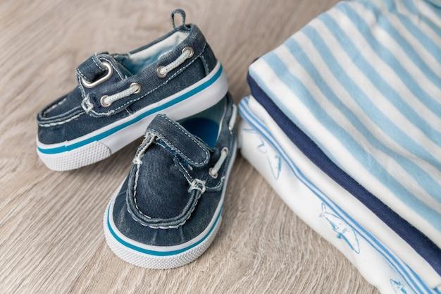 生まれたばかりの男の子のためのおむつに靴と折り畳まれた青と白のボディースーツ。幼児服のスタック。子供服。閉じる。